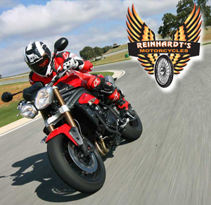 Photo of red Triumph on a Track with Reinhardts logo